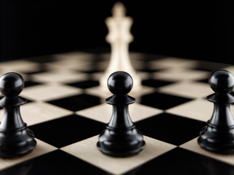Pawns and king chess pieces on chess board