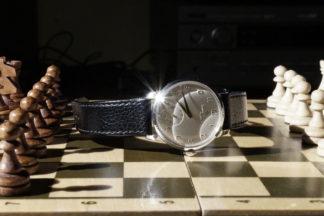 nadchodzi czas, początek szachowej partii, zdjęcie, fotografia, Tomasz Konopka, MDK Śródmieście Wrocław, pracownia fotograficzna, Piotr Kamiński, interaktywny podręcznik szachowy, lekcje szachowe, szachy dla dzieci, piękno w szachach, szachownica, zegarek, błysk, cień, białe i czarne bierki,