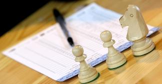 Blankiet zapisu partii szachowej, Mistrzostwa Europy Juniorów w szachach, Ryga, Łotwa, 2 runda, 21.08.2018, stół, długopis, białe bierki szachowe, dwa pionki i skoczek,