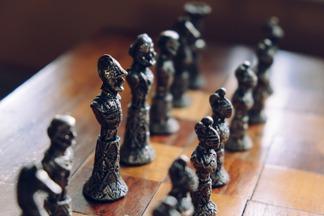 czarne bierki szachowe, szachownica,